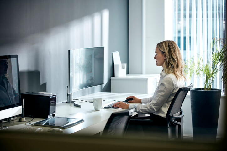 Female office worker using computer in office environment